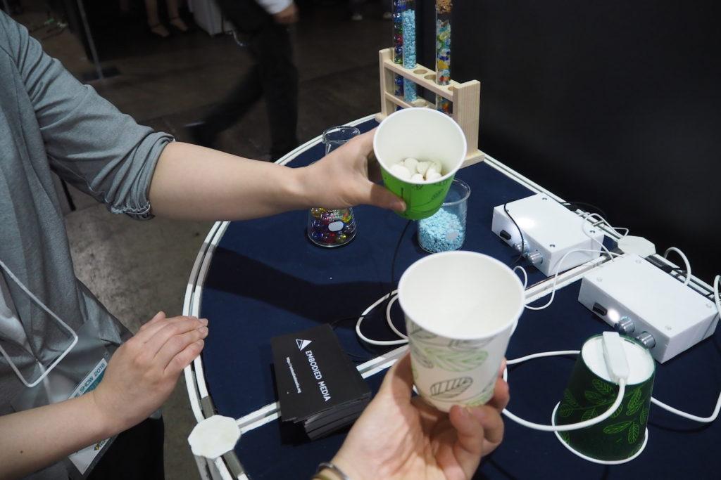 前述のテレイクジスタンスと同様の技術。片方のカップに小石などを入れると、もう片方のカップにその感触がリアルに伝わる。素材によって感じかたがまったく変わる。
